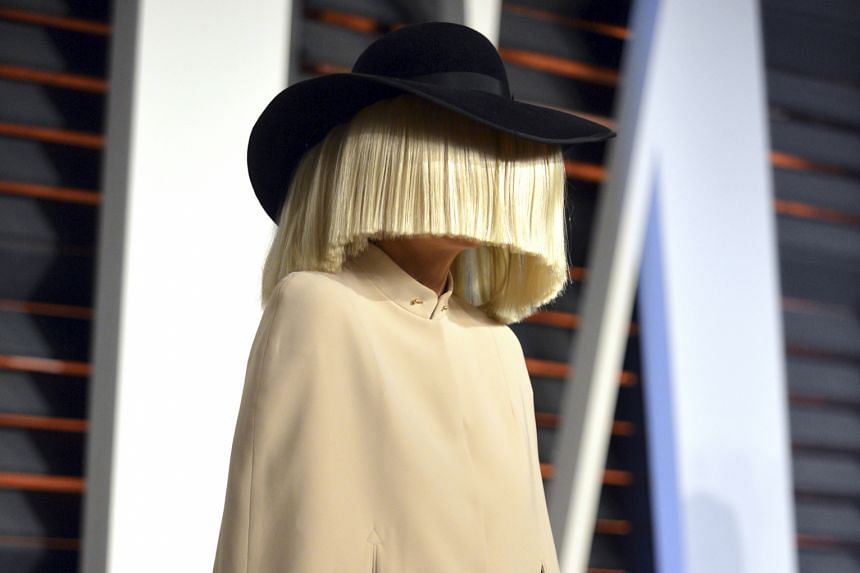 Singer Sia, who often hides her face (above)to preserve her anonymity, returns to dark territory on her latest album by exploring abusive relationships.