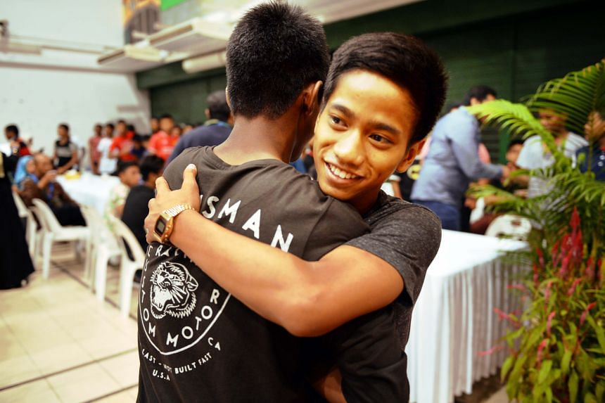 Haikal (right) hugging a friend. He received the Best Academic Award (N-levels) a day before he was discharged from Muhammadiyah Welfare Home.