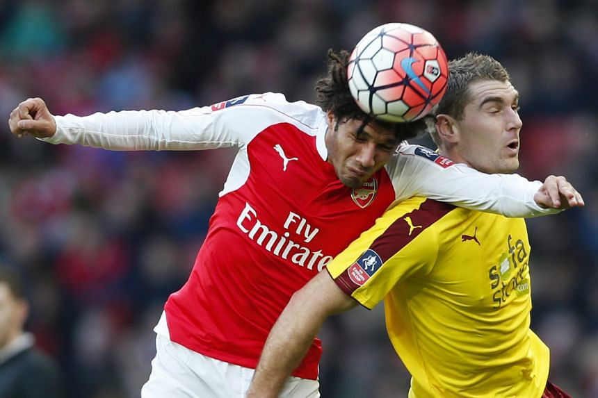 Mohamed Elneny (left), Arsenal's new €10 million (S$15.42 million) signing, gets the better of Burnley's Sam Vokes in the Gunners' 2-1 win in the fourth round of the FA Cup on Saturday.