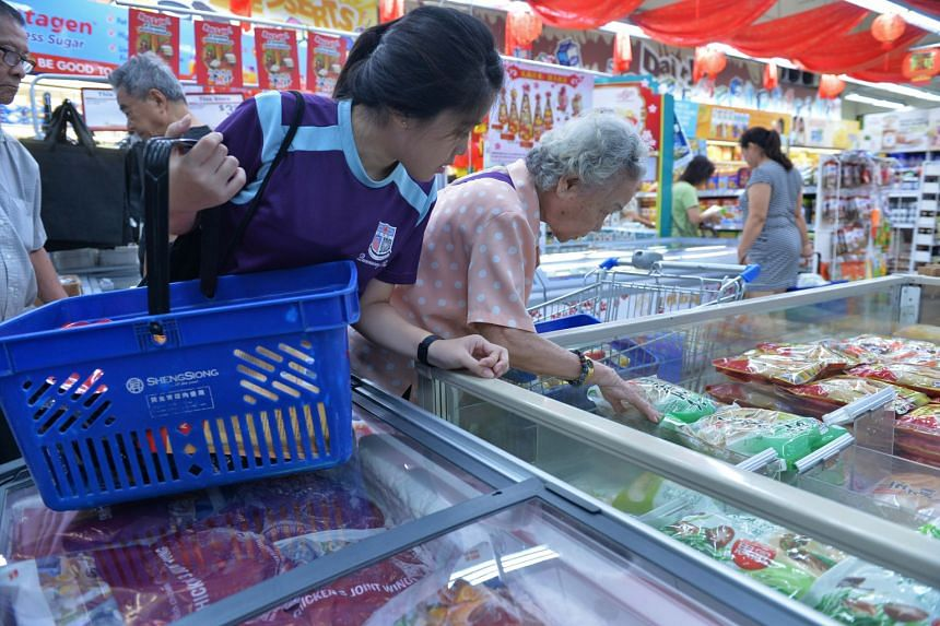 Queensway Secondary School student Ng Hui Yi, 16, helping Madam Poon Soo Lan, 88, with her grocery shopping. About 300 needy residents in Queenstown were treated to lunch and given a hongbao to buy groceries at an event yesterday. The red packet cont