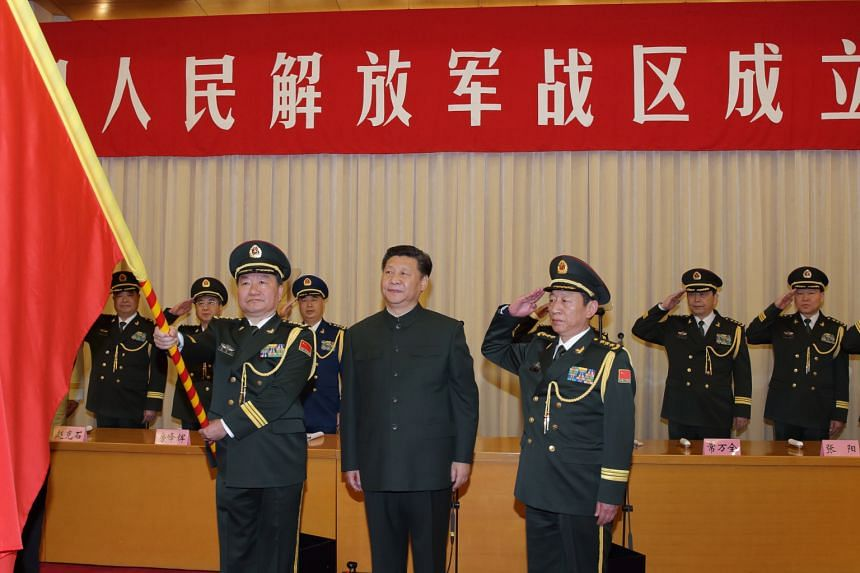 """Chinese President Xi Jinping (centre) during a ceremony yesterday to confer military flags on the five newly established """"theatre command"""" zones. With him are Commander Wang Jiaocheng (left) and Political Commissar Wei Liang."""