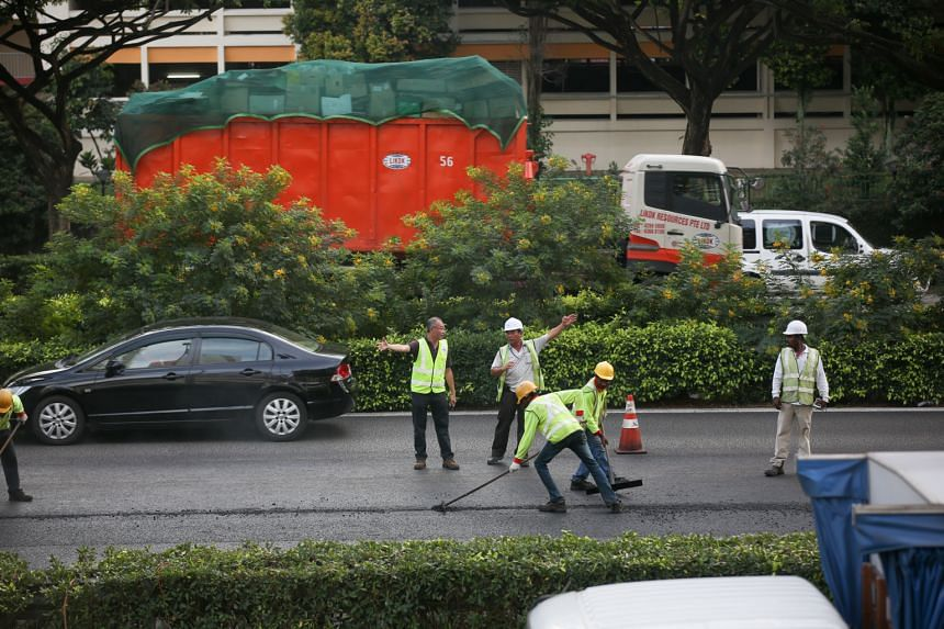 Workers resurfacing the affected section of PIE yesterday after the accident involving a tipper truck and an oil tanker caused the diesel spill. SCDF said it was alerted to the oil spill at around 1.40pm.