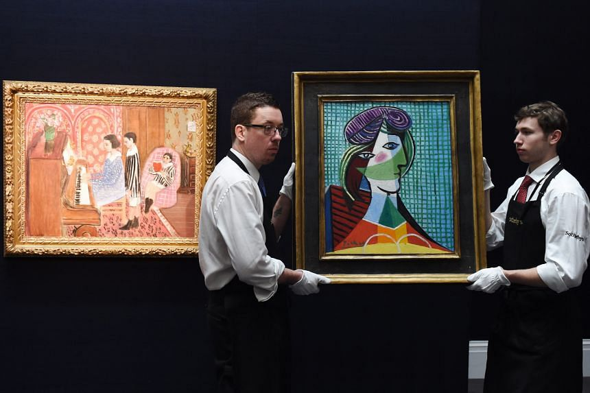Staff carry the painting Tete De Femme by Pablo Piccaso next to Henri Matisse's work La Lecon De Piano during a press preview at Sotheby's auction house ahead of its auction tomorrow.