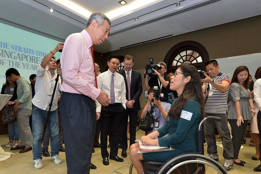 Prime Minister Lee Hsien Loong chatting with Paralympian Yip Pin Xiu, a finalist for The Straits Times Singaporean of the Year, at the awards ceremony yesterday. With them are (on PM's left) Mr Edmund Koh, UBS Singapore country head and head of UBS W