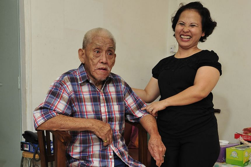 Madam Noriza with Mr Tan at his home, in a photo taken last year. Since her selfless act in 2014, she has spent nearly all her days off visiting him and his wife in their flat and later in hospitals and nursing homes.