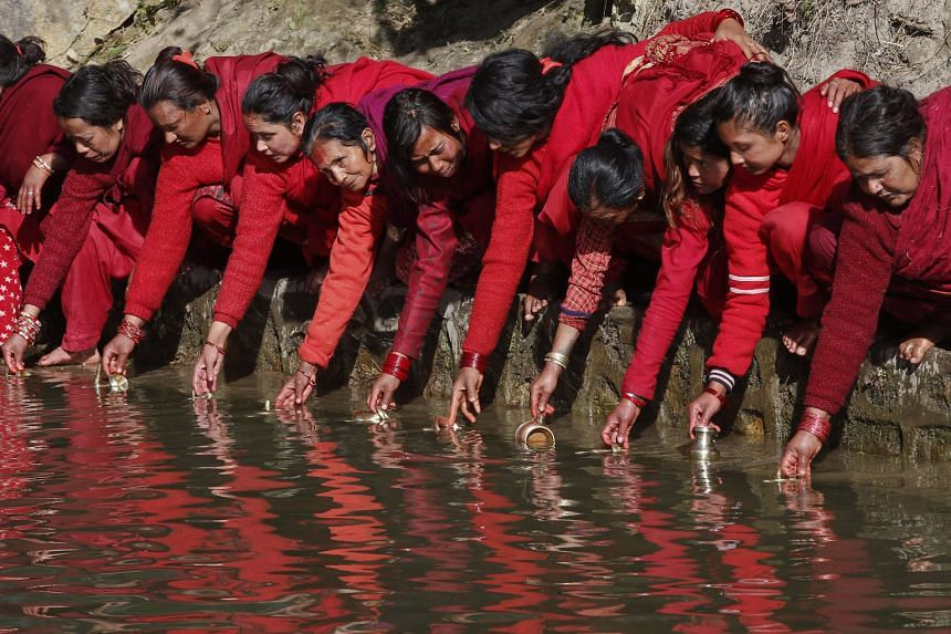 Nepalese Hindu women dressed in red collecting holy water during the Madhav Narayan Festival on Monday at Salinadi river in Sankhu near Kathmandu, Nepal. The festival marked the start of a month devoted to religious fasting, holy bathing and the stud