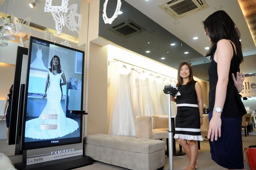 Writer Alyssa Woo is impressed with how the FXMirror got her measurements right. Ms Teo Pei Ru, owner of La Belle Couture Weddings, says the mirror lets customers try at least 15 dresses in 25 minutes.