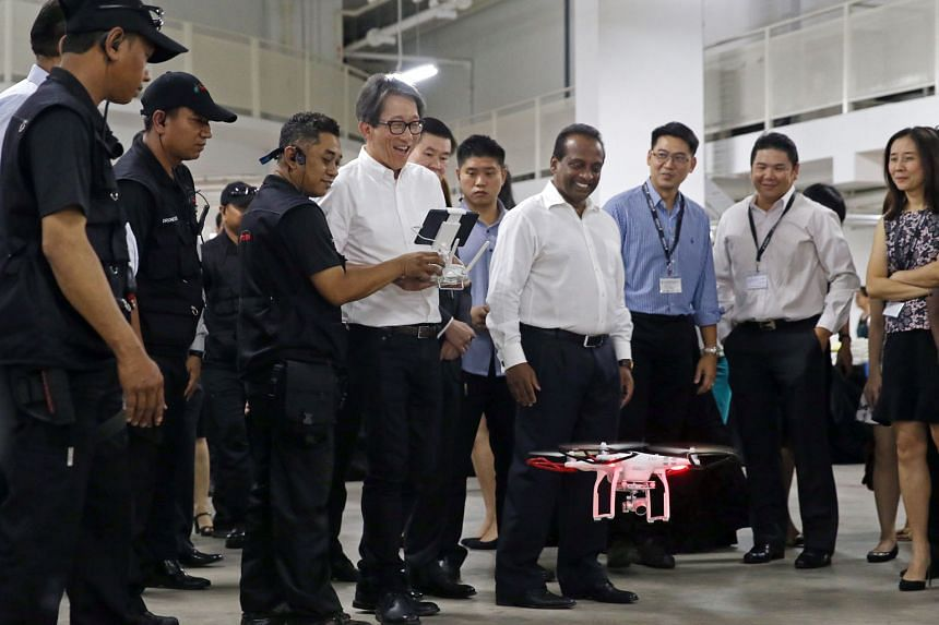 Left: Minister Lim attempts to fly a drone with the help of drone pilot Mohammad Romzi (to his right), as PestBusters' Mr Fernandez (to his left) looks on. Above: A PestBusters employee demonstrating the use of the drone to check for pests.
