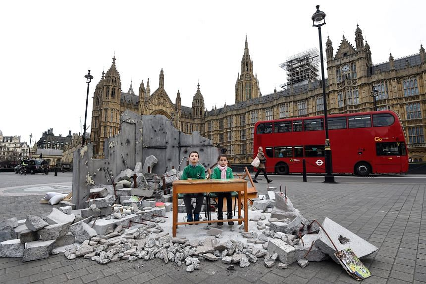 Abdallah, 12, and Dania, 10 - whose school in Aleppo, Syria, was bombed - sitting amid a mock-up of a destroyed classroom outside the Houses of Parliament in London yesterday. The photo-call was organised by Save The Children to highlight the need fo