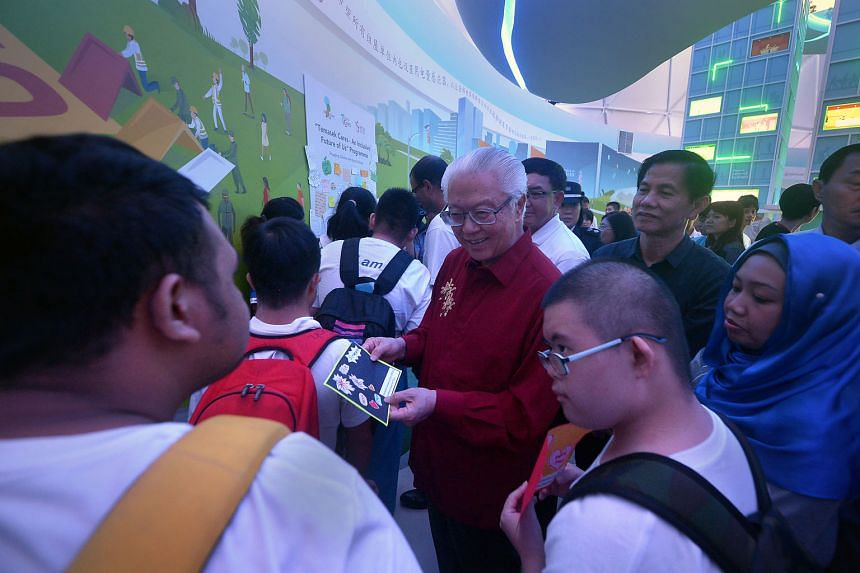 President Tony Tan Keng Yam chatting with students with special needs at the Home Tomorrow dome at The Future Of Us exhibition yesterday. The outing was part of an outreach programme that will benefit over 6,000 children with special needs.