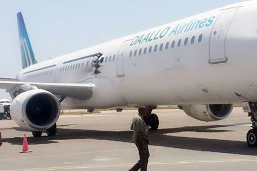 The Daallo Airlines plane (far left) made an emergency landing on Tuesday in the Somali capital of Mogadishu after a blast tore a 1m-wide hole (left) in the fuselage of the plane. Officials say one passenger was killed - the 55-year-old man was belie
