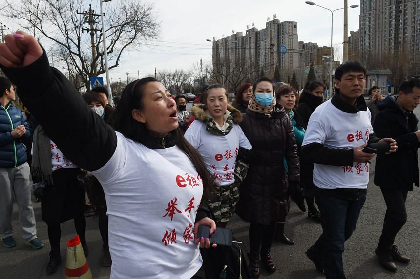 """Investors wearing T-shirts that read """"Ezubao: Raise hands, lose a family fortune"""" - a play on the company's slogan - protesting in Beijing yesterday against the P2P lender exposed as operators of a Ponzi scheme."""