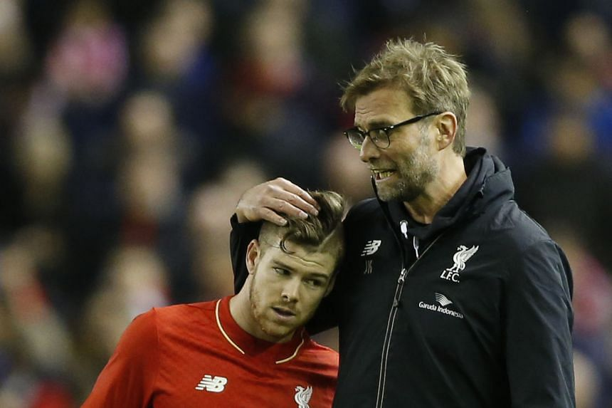 Reds manager Juergen Klopp speaking to defender Alberto Moreno. Klopp will hope his players can fight off fatigue against Sunderland today.