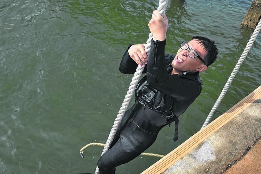 Trainees (above) covering themselves with sand during an exercise in the five-month Combat Diver Course. It was an equally gritty task for ST photojournalist Alphonsus Chern (left), seen here hauling himself up a rope at the Sembawang Camp jetty.