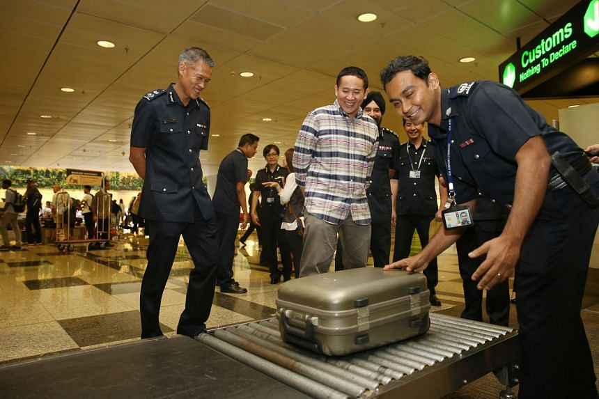 Mr Amrin, accompanied by ICA Deputy Commissioner of Operations Aw Kum Cheong (left), witnessing baggage screening at Changi Airport Terminal 3 yesterday.
