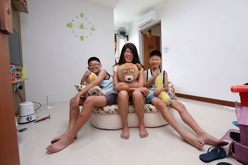 Ms Soh with her sons Brandon (left) and Bryan in the three-room Build-To-Order flat in Rivervale Crescent that they moved into last November. Ms Loh was able to afford the home with help from Central Provident Fund and Home Ownership Plus Education S