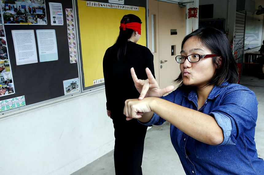 Miss Loh getting a participant, who is blindfolded and wearing earplugs, to experience what it is like to be deaf-blind, during her talk on Jan 31.
