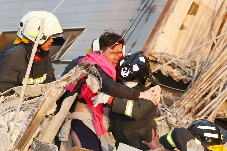 A rescue worker carrying a man from a collapsed building after a 6.4-magnitude quake struck Tainan City yesterday. By late yesterday, over 200 others had been rescued from the building.