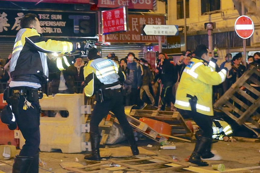 A policeman pointing his pistol (left) during the riot at Mongkok district in Hong Kong. Demonstrators charged police lines with home-made shields and set rubbish on fire in the worst street violence the city has seen since pro-democracy protests in