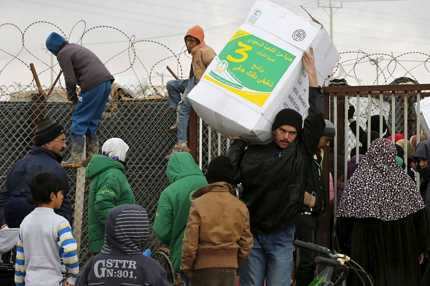 Syrian refugees receiving aid packages at a camp in Jordan near the border with Syria. Official statistics show Jordan has admitted 635,000 Syrian refugees. But the government says the real figure is around 1.4 million. This year alone, Jordan estima