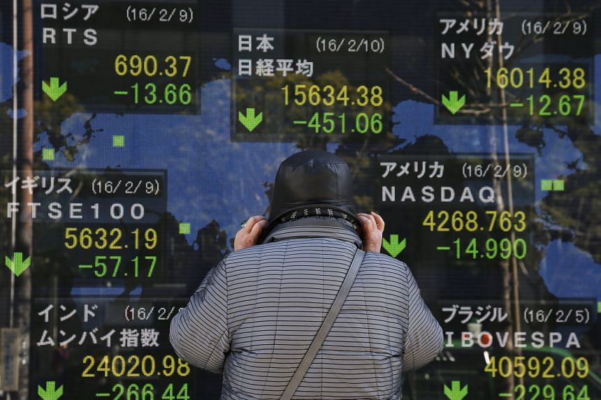 A man studying Nikkei Stock Average data in Tokyo yesterday. Banking stocks have been hit very hard since the central bank introduced negative rates.