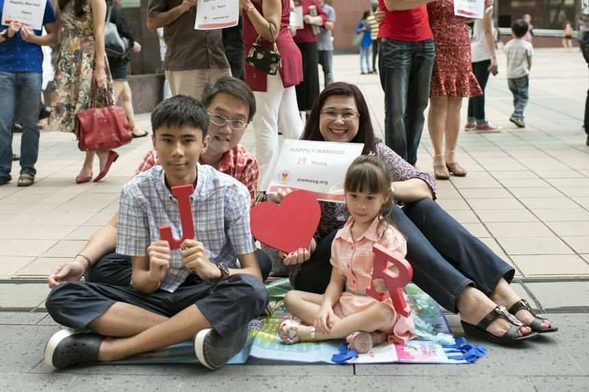 """Striking the """"love"""" pose to celebrate World Marriage Day are Ms Joyce Mehar and her husband of 19 years, Mr Ronald Khoo, as well as their children, 16-year-old Jeremy and four-year-old Ropheka."""