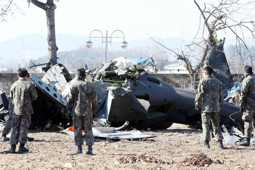 Rescue personnel surveying a crashed UH-1H military helicopter in a field in Chuncheon, in South Korea's north-eastern Gangwon province. The crash of the South Korean military helicopter yesterday killed three crew members and left one seriously inju