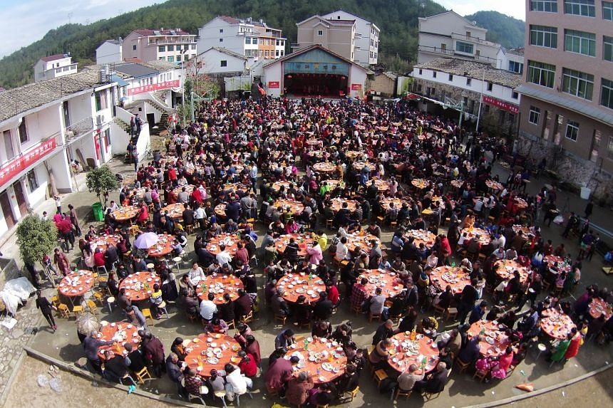 People turned up in force at a village square (top) to have lunch with family members and friends to celebrate the Spring Festival in Taizhou, Zhejiang province, last Thursday. Meanwhile, others queued to enter a shop (above) in Florentia Village in