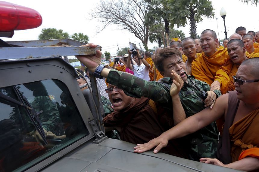 Buddhist monks in a scuffle with soldiers during a protest in Nakhon Pathom province west of Bangkok yesterday. Around 3,000 monks gathered for a seminar there to support abbot Somdej Chuang, the front runner for the post of Thailand's Supreme Patria