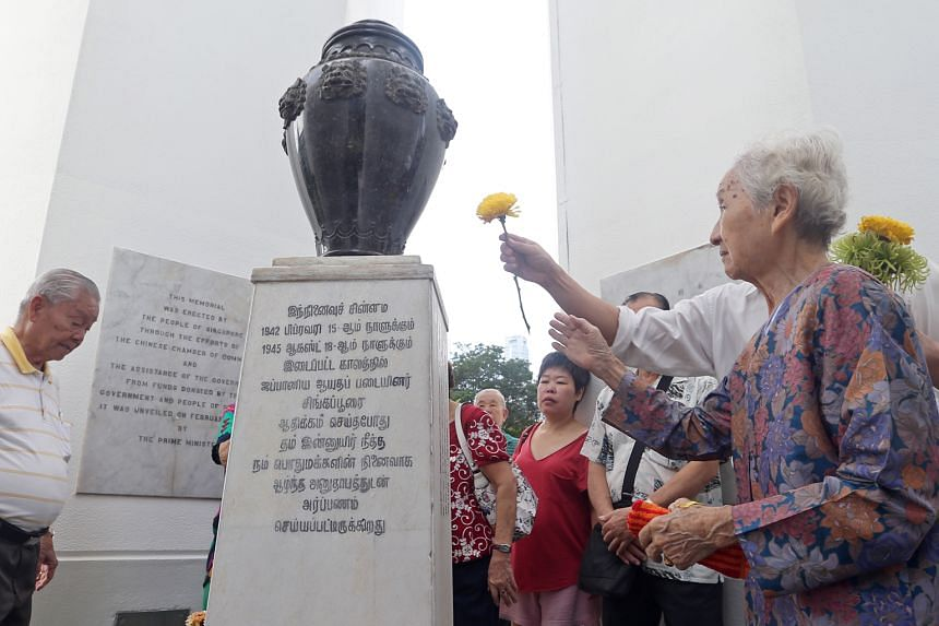 Madam Lim Geok Hong (right), 83, and her son John Teo (partially hidden, laying a flower), 50, at the Civilian War Memorial along with other participants of the 49th War Memorial Service yesterday.