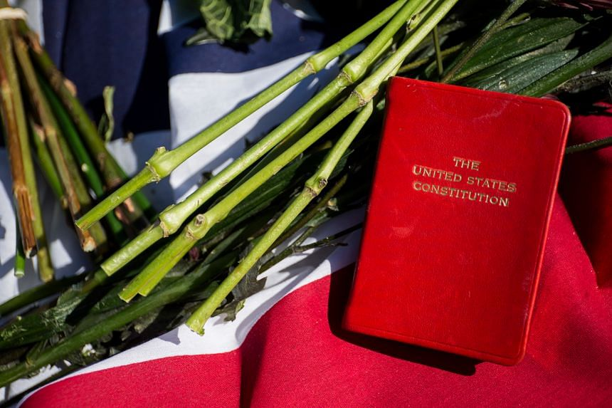 A copy of the US Constitution rests among tributes outside the Supreme Court in Washington for Justice Scalia, who died last Saturday. The White House has vowed to select a nominee within weeks.