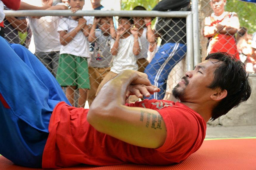 Children watch Manny Pacquiao work out at a sports complex in General Santos in the Philippines, in preparation for his April 9 bout against Timothy Bradley in the US.