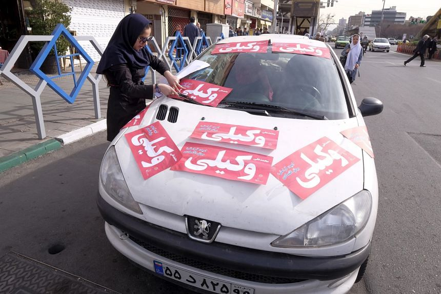 A woman in Teheran plastering her car with posters supporting Mr Mohammed Wakili, a candidate in the upcoming elections. Iran goes to the polls next week.
