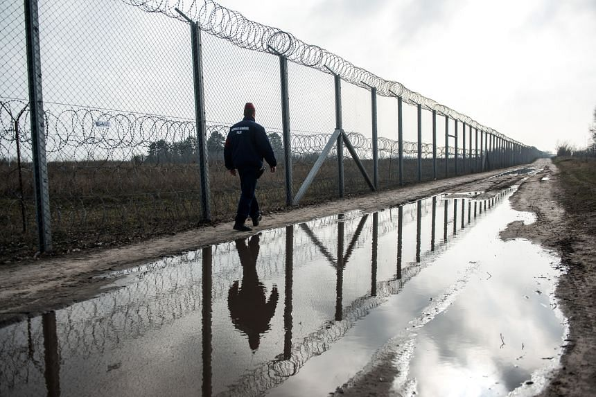 A member of the Hungarian police force on patrol along the razor wire-topped security fence on the Hungarian- Serbian border near Roszke, Hungary, on Wednesday. At the Brussels summit, Italian Premier Matteo Renzi warned eastern European leaders that