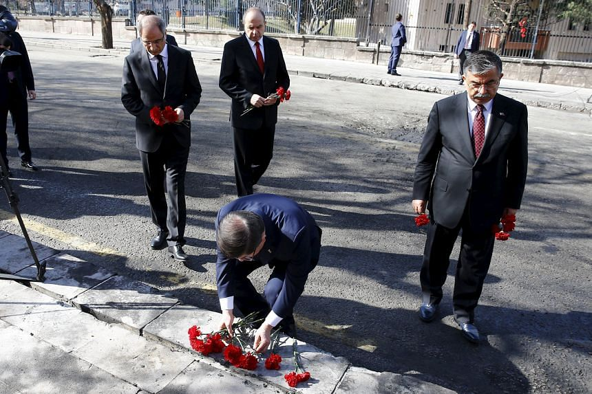 Turkish Prime Minister Ahmet Davutoglu placing flowers at the site of Wednesday's suicide bomb attack in Ankara that killed 28 people. Turkey says the YPG was behind the attack, but the US says it is not in a position to confirm or deny Ankara's accu