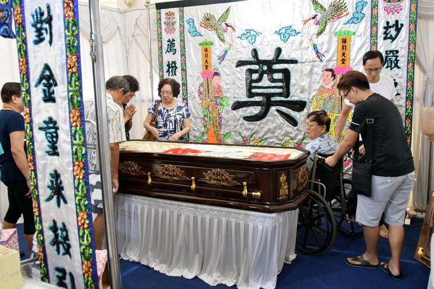 Mr Cheng Kiat Yan, Madam Tan Powi Kim's husband, in a wheelchair beside his wife's coffin at her wake in Tampines. Mr Cheng fractured his knee when he was thrown off his lorry in the accident.