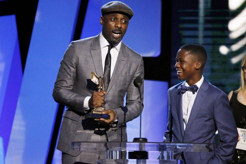 Idris Elba (left) accepting the award for Best Supporting Male for his role in Beasts Of No Nation as co-star Abraham Attah looks on.