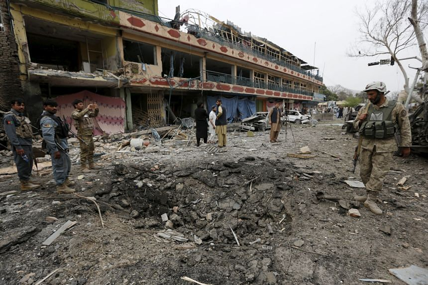 Afghan policemen inspect the site of the blast near the Indian consulate in Jalalabad.Two people were killed and 19 wounded. No group has claimed responsibility for the attack.