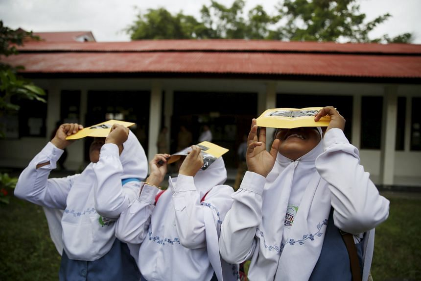 Students at a school in Ternate island, in eastern Indonesia, testing their self-made filters to look at the sun after a joint workshop between the Hong Kong Astronomical Society and Indonesia's National Institute of Aeronautics and Space. The total