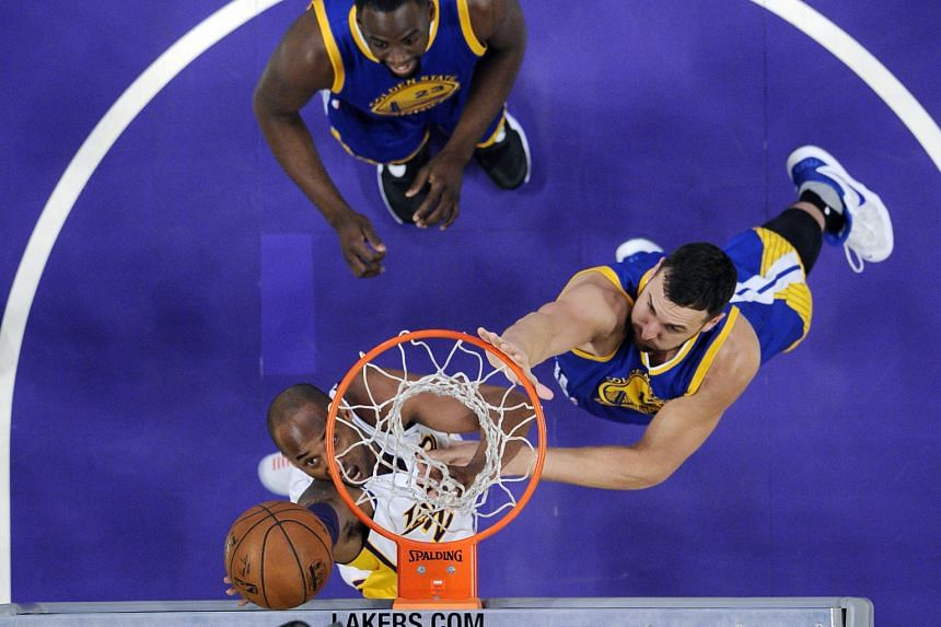 Kobe Bryant of the Los Angeles Lakers scoring against Andrew Bogut (right) and Draymond Green of the Golden State Warriors. The bottom-placed Lakers' 112-95 win over the table toppers is one of the biggest NBA upsets. The loss was just the Warriors'