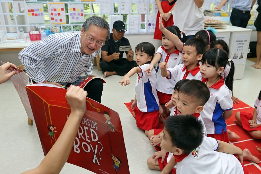 Mr Tan telling children in a K2 class, at the PAP Community Foundation (PCF) Sparkletots Preschool in Radin Mas yesterday, stories from What's Inside The Red Box. The book comes with pages for young readers to fill in their own hopes and dreams.