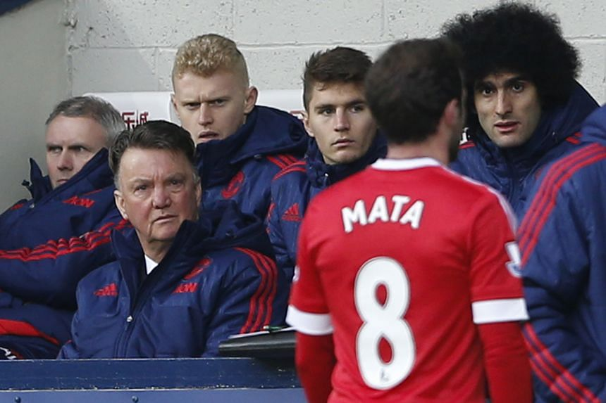Manchester United's Juan Mata walks down the tunnel after being sent off for the first time in his career as manager Louis van Gaal and United players look on.