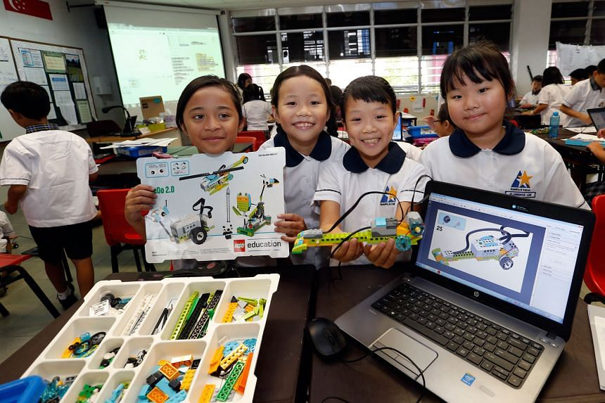 (From left) North View Primary School pupil Nurul Insyirah Jamaludin and her classmates, Chloe Lee, Olivia Koh and Florence Lee, all nine years old, showing off their robotic toy, which they built by tinkering with Lego bricks, motors and sensors. On