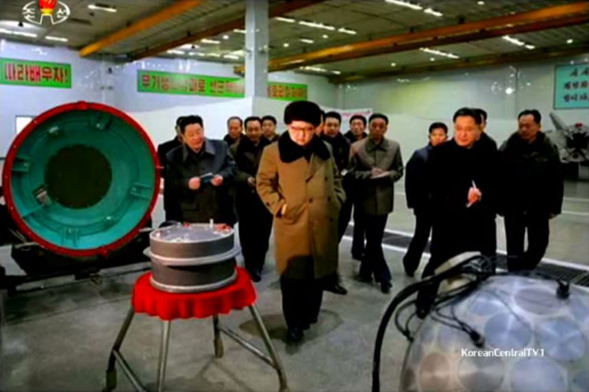 An image showing Mr Kim with parts said to be related to a warhead: a heat shield, a fuel-filled cylinder and a core sphere.