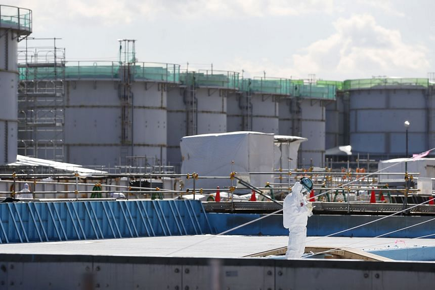 A worker in a protective suit and mask taking notes at the Fukushima No.1 nuclear power plant in Okuma town last month.