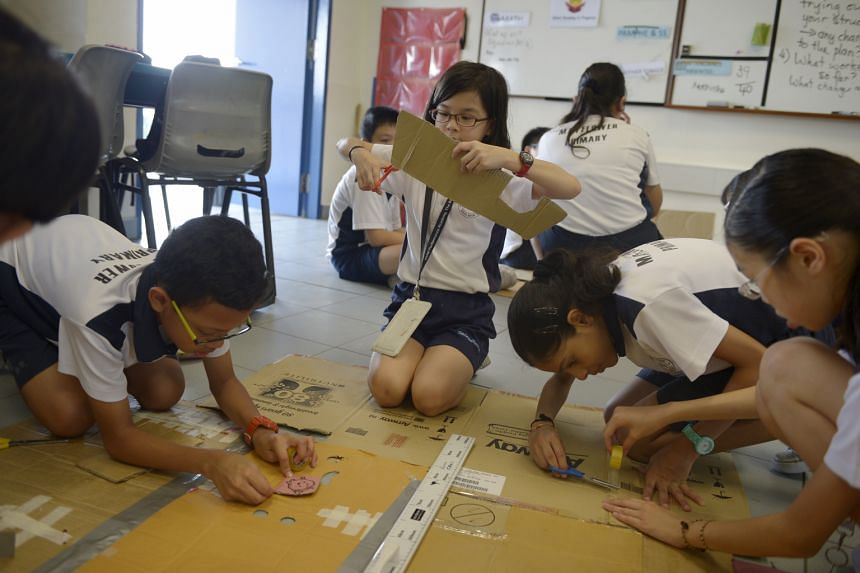 Mayflower Primary pupil Annabel Gan (centre), 12, cutting a piece of cardboard as classmates work on other parts of a prop. The project to design props for a skit teaches the children how to apply properties of a circle to a real-world context.