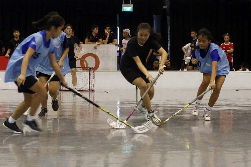 A player from Bellies (in black) controlling the ball as she defended against her opponents from Guji Guji in the girls' Under-21 final of the U Sports three-on-three floorball tournament yesterday at Downtown East. Bellies won the match 4-2. The sev