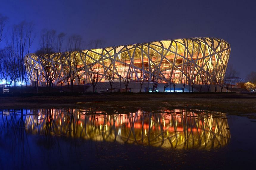 China's National Stadium, also known as the Bird's Nest, with its lights on (top) and off (above) during the annual Earth Hour event in the capital on Saturday. Millions of people around the world were expected to switch off their lights for Earth Ho