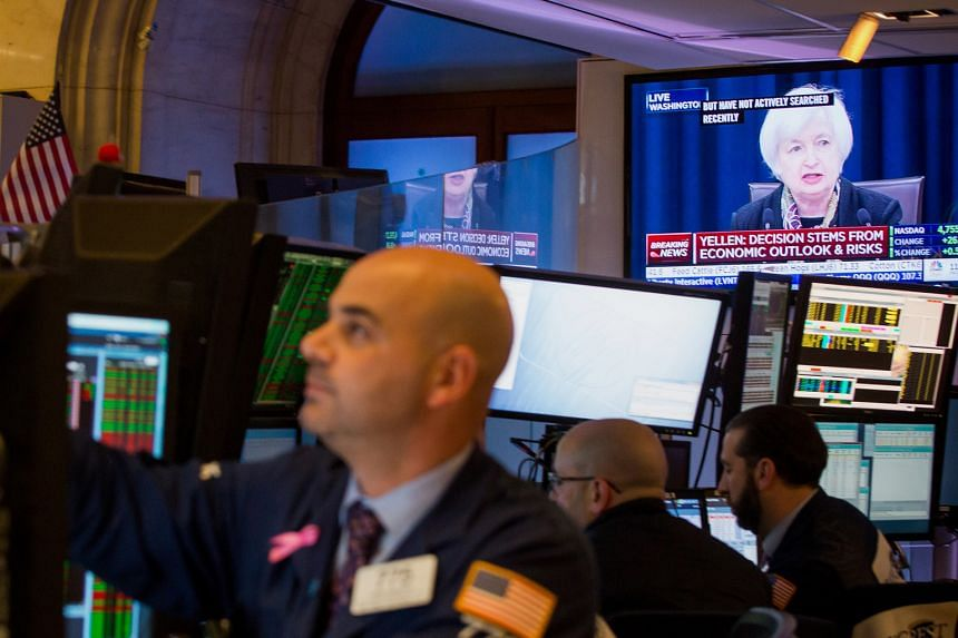 US Fed chief Janet Yellen, seen here on a television screen on the floor of the New York Stock Exchange on Wednesday, signalled a more gradual path of interest rate increases - from four rate hikes to only two. Investors are looking for clues if that