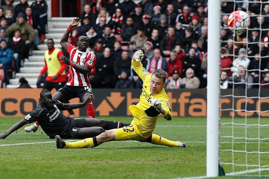 Southampton midfielder Sadio Mane raising his arm to celebrate after scoring their first goal past Liverpool goalkeeper Simon Mignolet. That sparked the Saints' rebound and they eventually claimed full points.
